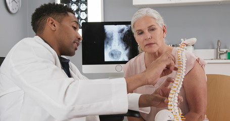 Senior female patient consulting with young doctor about back injury. Close up of black doctor holding model of spinal cord and explaining to elderly woman source of her pain