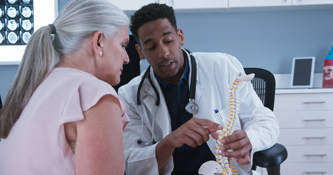 Young black medical doctor using sculpture of spinal cord to patient area of back injury. Senior female patient listening to doctor explain reason for her back pain