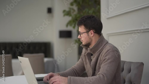 A man in glasses is working on the computer while someone