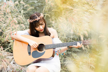 Asian beautiful woman wearing bohemian clothes Are practicing playing the guitar in the morning In the grasslands during the summer holidays Is relaxing from stressful matters Makes you feel happy