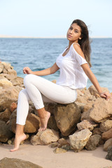 Beautiful young girl face portrait, brown hair and nice smile, wearing white tunic, fashion model look with a sea landscape. Female woman photo session for fashion beauty competition, middle eastern