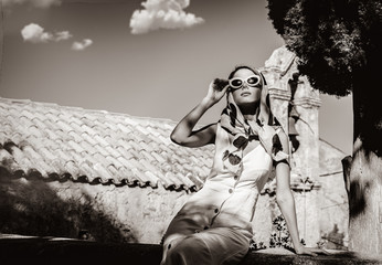 Young girl dressing in 60s style clothes in a village with old church on background. Crete, Greece