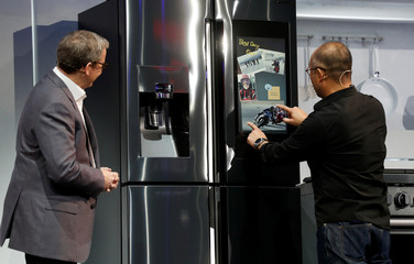 """Samsung's John Herring looks on as Yoon Lee, a Samsung senior vice president, adjusts a photo on the """"Family Board"""" of a  Family Hub smart refrigerator during a Samsung news conference at the 2019 CES in Las Vegas"""