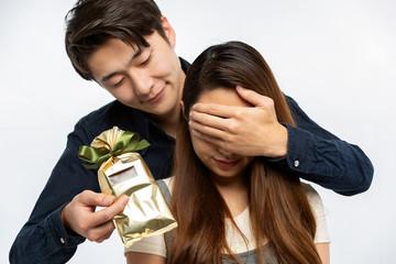 女性に目隠しをしてサプライズプレゼントを渡す男性