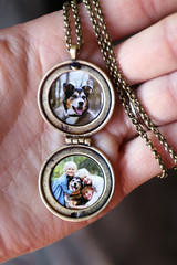 Woman's Hand Holding Antique Locket with Photos of Children and Pet Dog Inside