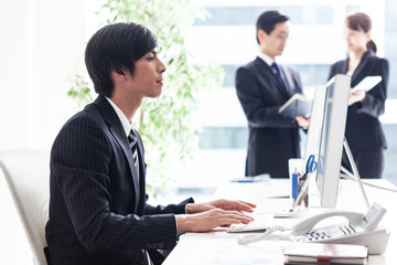 窓際の明るいデスクでパソコン業務を行う男性会社員