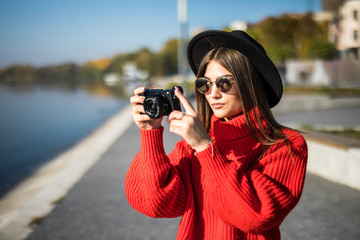 Young pretty woman in black hat and sunglasses taking photo with camera at city promenade pier.
