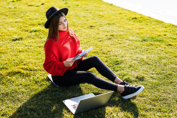 Attractive casual student woman lying on grass taking notes on campus at college