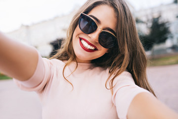 Closeup selfie-portrait of attractive girl in sunglasses with long hairstyle and snow-white smile in city.