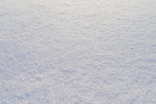 High angle view of snow texture, background with copy space. Snow texture or winter white background with grain rough pattern