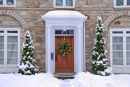 stone fronted house with snow and wreath on front door