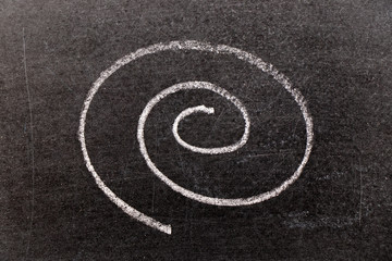 White chalk hand drawing in spiral shape on black board background