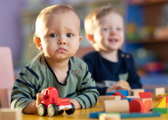 Baby boys with toy car and building blocks in kindergarten