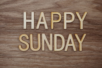 Happy Sunday text message on wooden background