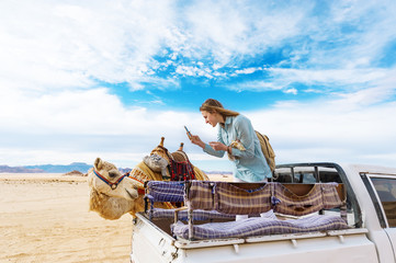 The young woman photographs a camel from a car body in the Jordanian desert