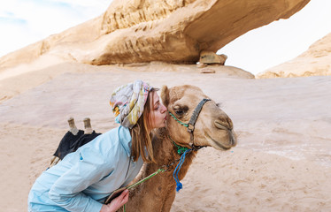 The woman touches with lips a muzzle of a camel in the Jordanian desert.