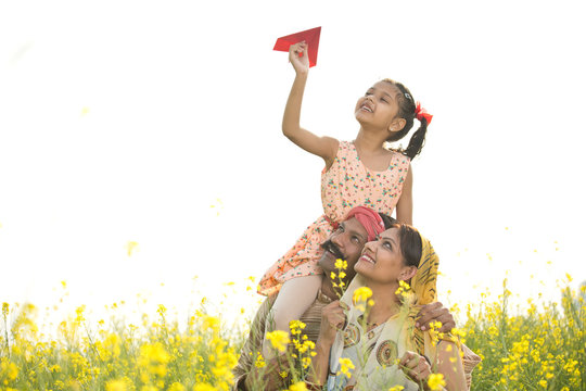 Girl sitting on father's shoulder and throwing paper airplane