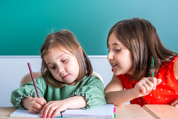older sister looks at her younger sister as she draws in a notebook