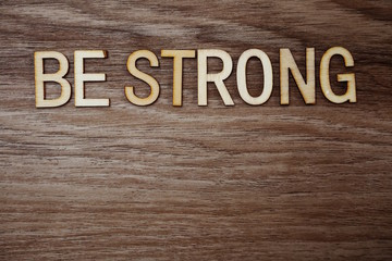 Be Strong alphabet letters on wooden background business concept