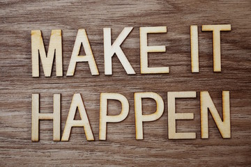Make It Happen text message on wooden background