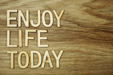 Enjoy Life Today text message on wooden background