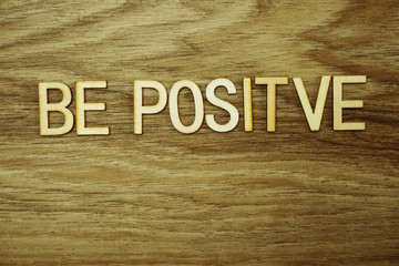 Be Positive text message on wooden background