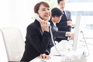 笑顔で電話対応をする明るい女性