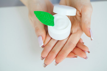 Close-up of a woman hand holding a container of moisturizer cream