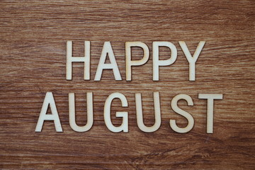 Happy August text message on wooden background
