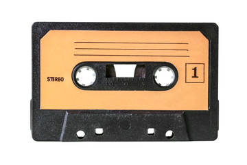 An old vintage cassette tape from the 1980s (obsolete music technology). Black grid plastic body, pale orange label with lines for taking notes and the text Stereo, one.