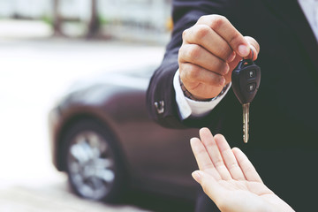 Car key, businessman handing over gives the car key to the other woman on car background. Wall mural