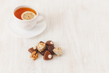 Chocolate candy with nuts, cup of hot tea with lemon and saucer on white wooden table, selective focus.