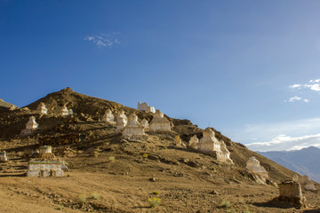 ancient white Tibetan Buddhist temples stupas on the slope of a desert hill against the blue sky and mountain valley