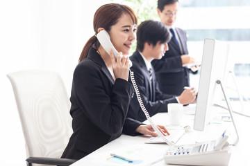 笑顔で電話対応をする女性会社員