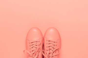 Pair of coral shoes on coral background. Trendy color of 2019. Monochrome image.