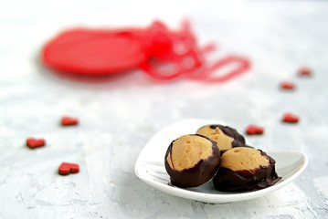 Homemade candies Buckeyes of peanut butter, covered with dark chocolate, on a gray background. Valentine's day concept.