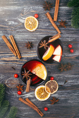 Christmas mulled wine with spices, orange slices, cinnamon sticks and fir branches on wooden table. Traditional drink on winter holiday. Top view, rustic style.