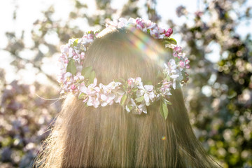 Blonde woman with a wreath of flowers in hair, back view