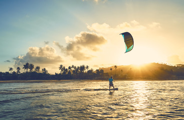 A young man is riding a kite-surf on the sea lagoon against the backdrop of sunset and palm trees