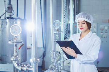 A young beautiful girl in white overalls makes notes in a tablet on the background of equipment of a food processing plant. Quality control in production