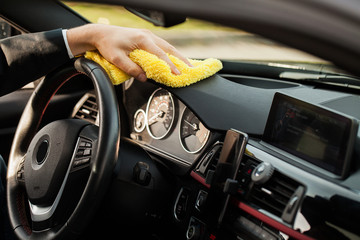 Clining car. Wiping panel of a luxury car with yellow microfiber, close-up view