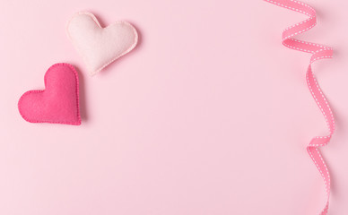 Pink felt hearts and ribbon on pastel background with empty space for text.