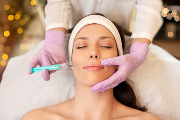 people, beauty, cosmetology and technology concept - beautician with syringe doing hyaluronic acid injection for lip augmentation to young woman
