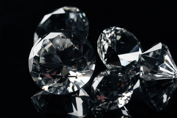 close up of collection of pure shiny diamonds isolated on black