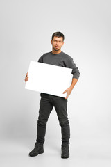 Positive smiling handsome man wearing grey casual clothes is holding white big mockup poster isolated on grey white background