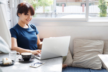 Asian young woman holding credit card mockup and using laptop computer while sitting in cafe. Online shopping concept. Copy space. Selective focus.