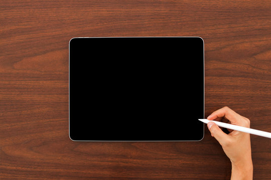 Mock up of digital tablet device with digital pencil in hand on wooden background. Laptop and digital pen connecting wifi.  Flat lay, Top view. Copy space.