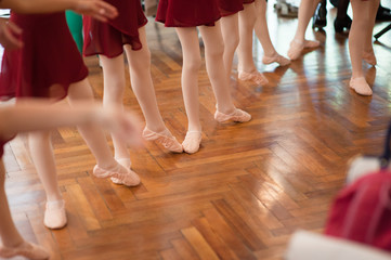 legs and feet of group of young ballerina girls on parquet in dance school indoors