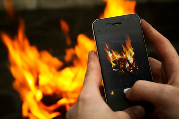 Men's hands take pictures of a bonfire on a mobile phone
