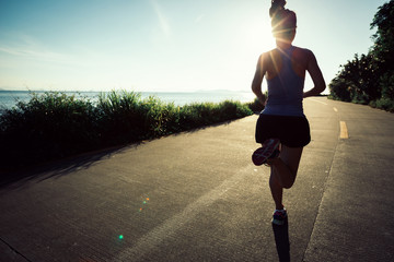 Fitness woman running on seaside trail in the morning
